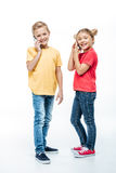 Kids talking on mobile phones. Happy kids talking on mobile phones and looking at camera isolated on white stock images