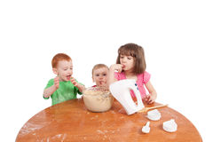 Kids tasting cake mix Stock Photos