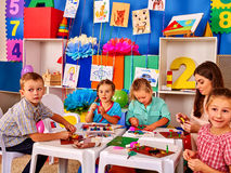 Kids with teacher are making something out of colored paper. Royalty Free Stock Photo