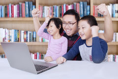 Kids and teacher raise hands in library. Image of two happy students and their teacher celebrate winning while looking at the laptop and raise hands in the stock image