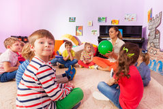 Kids and teacher sit in circle. Large group of kids boys and girls sit together in kindergarten class and play word game with ball Stock Photography