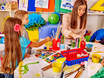 Kids with teacher woman painting on paper in  kindergarten . Royalty Free Stock Image