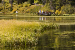 Kids and Teachers at lake in Autumn. Kids and teachers stand on wooden dock looking into a lake surrounded by autumn colors Stock Photo