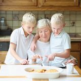 Kids teaching grandma to use tablet pc. Teenager boys twin brothers teaching grandmother to play on tablet pc, enjoying time together, eating cookies and Stock Images