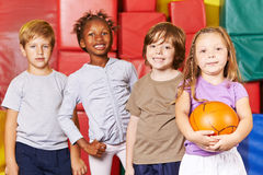 Kids team with ball in gym. Smiling kids team standing with ball in a gym of a preschool stock photos