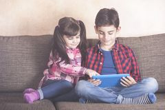 Brother and sister using tablet at home. Kids and technology concept with kids having fun with their tablet Stock Images