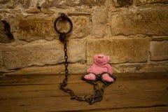 Kids teddy bear prisoner in jail chains. Kids pink teddy bear chained to wall in jail as prisoner Stock Photo