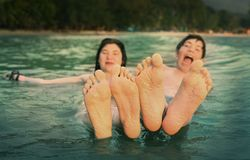 Kids teenager feet close up photo in the sea on the tropical beach. Background Royalty Free Stock Images