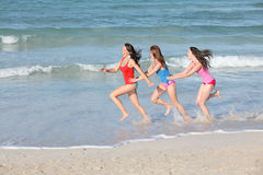 Kids, teens running on beach vacation. Group of happy kids, teens, youth teenagers running up beach on summer holiday or vacation or spring break Royalty Free Stock Photo