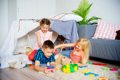 Kids in a teepee. Portrait of three kids in a teepee in a living room Stock Image