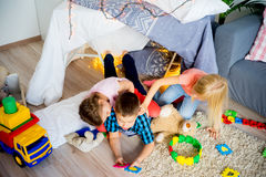 Kids in a teepee. Portrait of three kids in a teepee in a living room Stock Photos