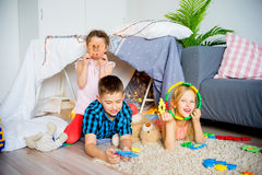 Kids in a teepee. Portrait of three kids in a teepee in a living room Stock Photo