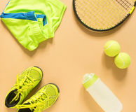 Kids tennis stuff on cream background. Sport, fitness, tennis, healthy lifestyle, sport stuff. Tennis racket, lime trainers, tenni Royalty Free Stock Images