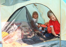 Kids in a tent. Little girl and boy - kids sitting inside modern tent stock images