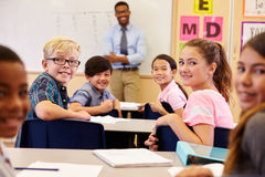 Kids at their desks in classroom turning to face the camera Stock Image