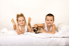 Kids with their kitten on the bed royalty free stock images