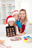 Kids with their mother making christmas cookies Stock Images