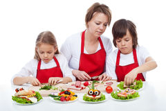 Kids and their mother preapring the party sandwiches Stock Images
