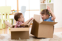 Kids in their new home having fun with cardboard boxes Stock Images
