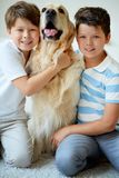 Kids and their pet. Portrait of happy siblings with their pet looking at camera at home Stock Photos