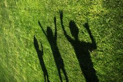 Kids with their shadows on grass. silhouettes of three persons standing with their hands stretched up stock photo