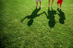Kids with their shadows on grass. silhouettes of three persons standing with their hands stretched up royalty free stock photography