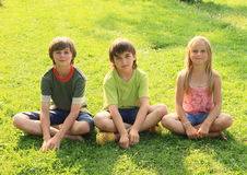 Kids. Three little kids - two boys and girl sitting on green grass Stock Image
