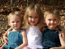 Kids three siblings. Three kids in a row, brother sister and brother Royalty Free Stock Images