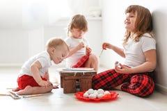 Kids three siblings  paint  eggs, Easter Royalty Free Stock Photos