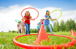 Kids throw colorful hoops on cones while competing Royalty Free Stock Photos