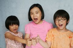Kids with thumbs up. Portrait of three children laughing and giving the thumbs-up sign Stock Images