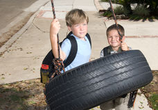 Kids and tire swing. Two kids play on a tire swing after school Royalty Free Stock Photo