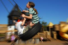 Kids on tire swing. Young kids having fun on tire swing Royalty Free Stock Images