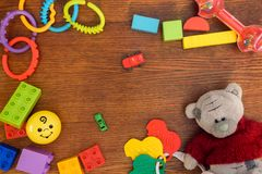 Kids toys background. Colorful toys, Teddy Bear,construction blocks and cubes on wooden table. Top view. stock photos