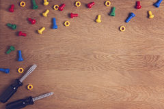 Kids Toys Background Frame Boarder with colorful nuts, bolts and two screwdrivers on wooden table. Top view. Flat lay Royalty Free Stock Photo
