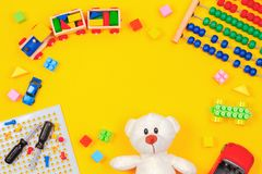 Kids toys background. Teddy bear, wooden train, colorful blocks, toy tools kit, cars, abacus on yellow background. Top view royalty free stock image