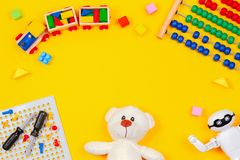 Kids toys background. Teddy bear, wooden train, robot, colorful blocks, toy tools kit, abacus on yellow background. Top view stock photography