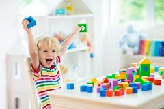 Kids toys. Child building tower of toy blocks stock image
