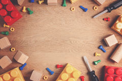 Kids toys frame background. Colorful toy tools, construction blocks and cubes on wooden table. Top view. Flat lay. Copy Stock Image