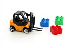 Kids toys. Yellow forklift toy ships color cubes stock photo