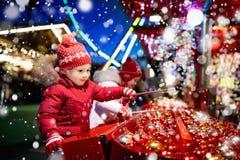 Kids at Christmas fair. Children shopping xmas gifts. Stock Photos