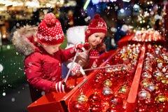 Kids at Christmas fair. Children shopping xmas gifts. Royalty Free Stock Image