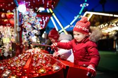 Kids at Christmas fair. Children shopping xmas gifts. Kids at traditional Christmas fair. Children and Xmas market on snowy evening. Family shopping Christmas royalty free stock images
