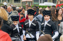 Kids in traditional Georgian costumes going to crowd of people royalty free stock photography