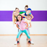 Kids train Zumba fitness in dancing school Stock Photo