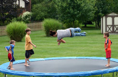 Kids on Trampoline. Four children having a great time jumping on trampoline royalty free stock images