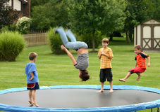 Kids on Trampoline. Four children having a great time jumping on trampoline stock image