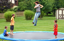 Kids on Trampoline. Four children having a great time jumping on trampoline royalty free stock image