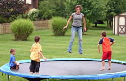 Kids on Trampoline. Four children having a great time jumping on trampoline royalty free stock photo