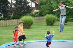 Kids on Trampoline. Four children having a great time jumping on trampoline royalty free stock photos